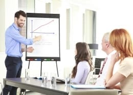 man using whiteboard to show graph to others